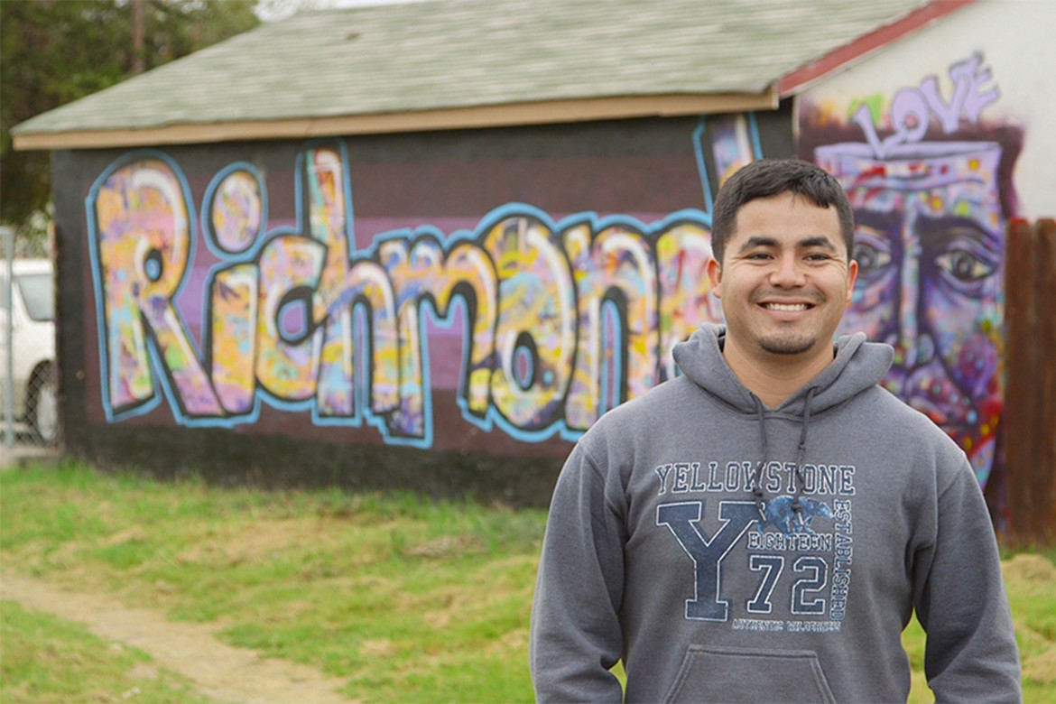 Javier Ochoa Reyes, Groundwork Richmond project coordinator, in front of Richmond Greenway mural