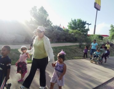 Residents of Denver's Globeville neighborhood walk along the South Platte River walking/biking path.