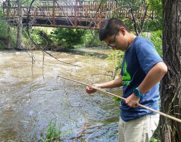 Groundwork Denver Blue Team member Fernando Chavez collecting a water sample from the Bear Creek in Sheridan
