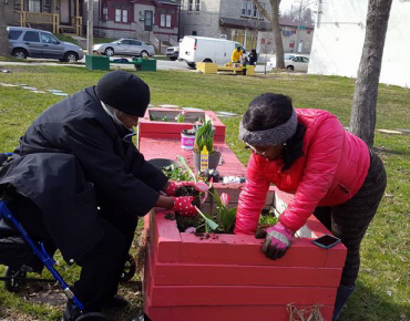 Women planting flower bed in Milwaukee's 2nd Street Pocket Park, designed as a safe area for children and families
