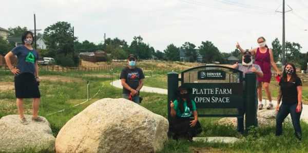 Groundwork Denver staff in front of Platte Farm Open Space sign
