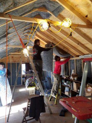 Installing denim insulation in learning center