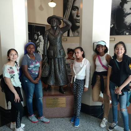 students pose with statue of first female immigrant at Ellis Island National Museum