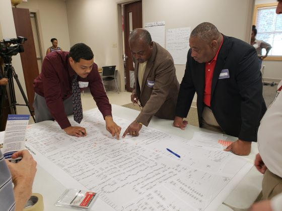 Local community stakeholders engage in a dot mapping exercise to prioritize development of sites in the Four Corners neighborhood.